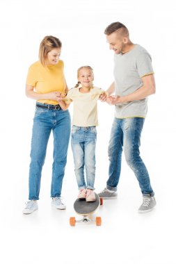 smiling family holding hands of little daughter on skateboard isolated on white
