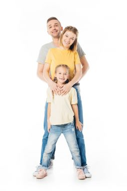 smiling parents and little daughter hugging each other and looking at camera isolated on white