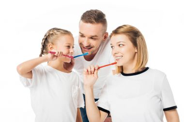 portrait of family in similar clothing brushing teeth isolated on white