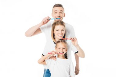 portrait of smiling family in similar clothing with toothbrushes isolated on white