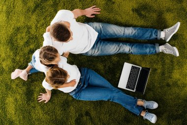 overhead view of family with laptop resting on green lawn