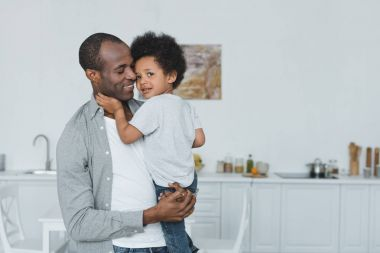 african american father hugging son at home