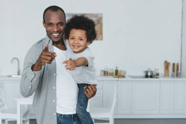 african american father and son pointing on camera at home