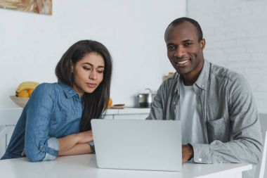 African american couple using laptop at table at home stock vector