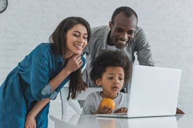 Smiling family looking at laptop