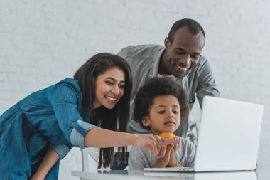 african american mother pointing on something at laptop at home