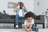 Fotografia afroamericano infelice padre che gioca video gioco e figlio disegno sul pavimento nel paese