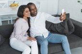 Fotografia ragazza afro-americana e il ragazzo prendendo selfie sul sofà a casa