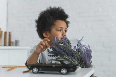 adorable african american boy touching violet flowers and looking away at home