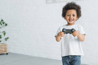 smiling adorable african american boy standing with joystick at home