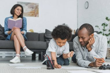 african american father drawing with son and mother reading book at home