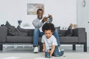 african american father playing video game and son drawing on floor at home