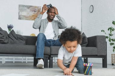 unhappy african american father playing video game and son drawing on floor at home