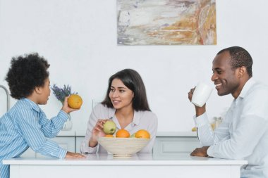 african american parents and son having breakfast at table in kitchen