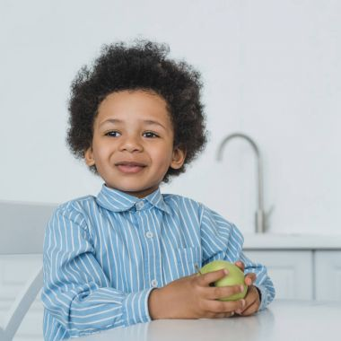 adorable african american boy holding apple at table in kitchen