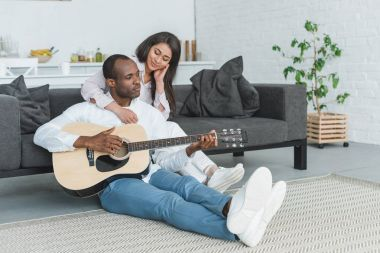 african american boyfriend sitting on floor and playing guitar for girlfriend at home