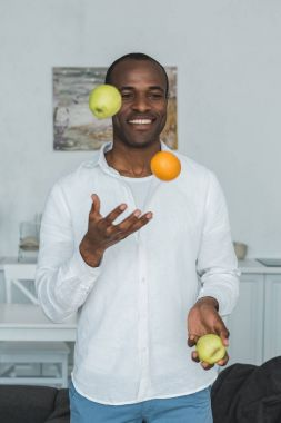 Handsome african american man juggling with fruits at home stock vector