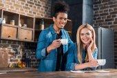Fotografie Porträt des Lächelns multirassische junges Paar mit Tassen Kaffee in der Küche zu Hause