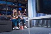 Fotografie Gemischtrassige paar Angst mit Popcorn gerade Sport auf Sofa zu Hause zusammenpassen