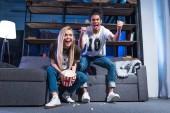 Fotografie Gemischtrassig Brautpaar mit Popcorn beobachten Sport passen zusammen zu Hause auf sofa