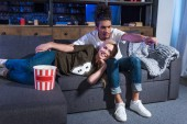 mnohonárodnostní mladý pár s popcorn sledovat film na pohovce spolu doma