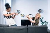 Fotografie mladý pár mnohonárodnostní hrát spolu na pohovce doma