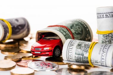 close-up view of rolled dollar banknotes, small red car model and bitcoins isolated on white