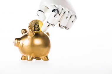 robotic arm putting bitcoin into golden piggy bank isolated on white