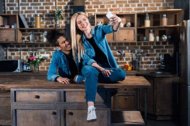 multiethnic smiling couple taking selfie on smartphone together in kitchen