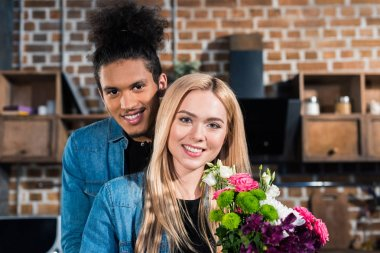 portrait of happy caucasian woman with bouquet of flowers and african american boyfriend near by in kitchen at home