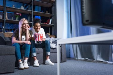 smiling multiracial couple with popcorn watching film on sofa together at home