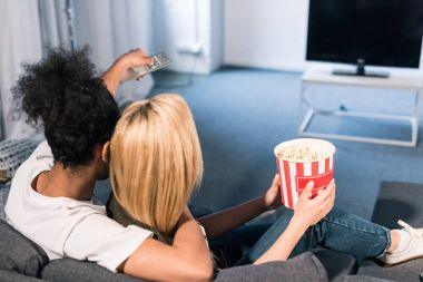 back view of multiracial couple with popcorn watching film together at home