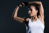 Photo strong sportswoman showing muscular biceps, isolated on grey