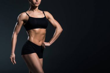 cropped view of sexy female bodybuilder with sexy muscular body,  isolated on grey