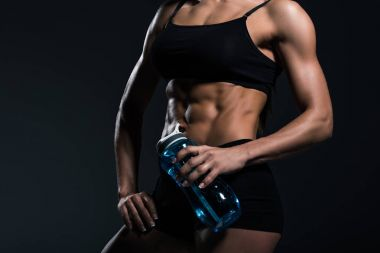 cropped view of muscular sportswoman with sport bottle, isolated on grey