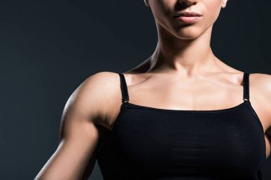 cropped view of muscular sportswoman,  isolated on grey