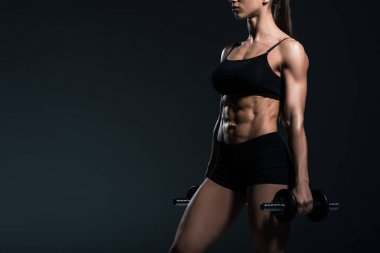cropped view of muscular sportswoman training with dumbbells, isolated on grey
