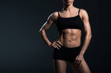 cropped view of female bodybuilder standing sportswear,  isolated on grey