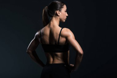 back view of beautiful bodybuilder with muscular body in sportswear,  isolated on grey