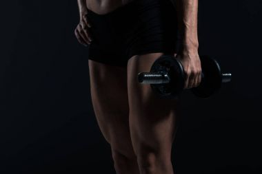 cropped view of female bodybuilder holding dumbbell, isolated on grey