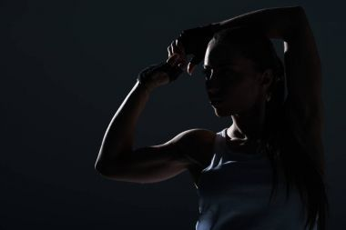 silhouette of strong sportswoman showing muscular biceps, isolated on grey