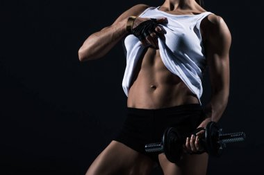 cropped view of sportswoman with dumbbell showing muscular abs, isolated on black