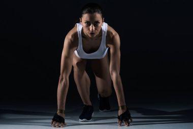 beautiful athletic woman ready to run, on black