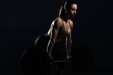 beautiful female bodybuilder lifting barbell, isolated on black