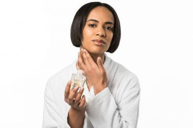attractive african american woman applying perfume on neck,  isolated on white