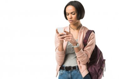 confused african american student with backpack using smartphone,  isolated on white