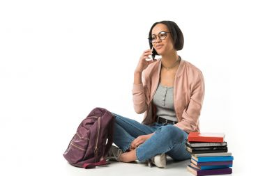 female african american student talking on smartphone and sitting with backpack and books on floor, isolated on white
