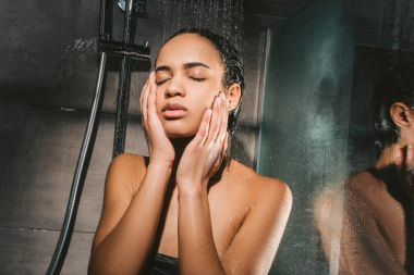 tired african american woman washing body in shower