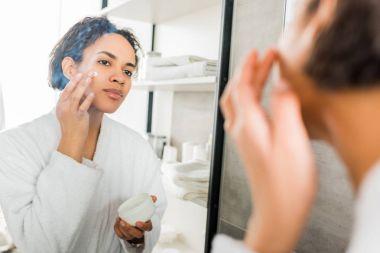 selective focus of african american girl applying moisturizing cream on face in bathroom near mirror