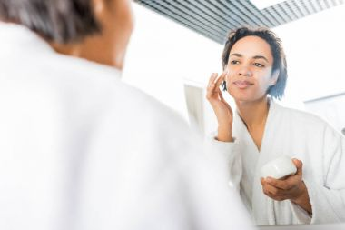 selective focus of smiling african american woman applying face cream near mirror in bathroom